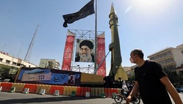 """صاروخ """"شهاب 3"""" معروضا بجانب صورة لخامنئي في اطار معرض شارع نظمه الجيش الإيراني وقوات الحرس الثوري في ساحة بهارستان في طهران، للاحتفال بـ""""أسبوع الدفاع""""  (25 ايلول 2021، أ ف ب)."""