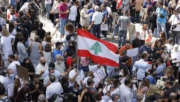 العلم اللبناني مرفوع وسط تظاهرة أمام قصر العدل في بيروت اليوم (مارك فياض).
