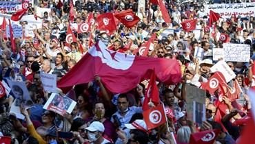 تونسيون يرددون شعارات مؤيدة للرئيس سعيد خلال تجمع حاشد في شارع الحبيب بورقيبة بالعاصمة تونس (3 ت1 2021، أ ف ب).