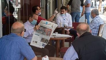Un homme lit le journal Annahar dans un café (Nabil Ismail).