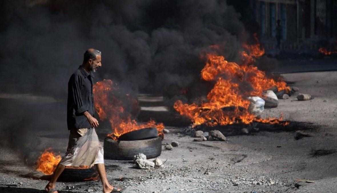 رجل يمني يمر بجوار الإطارات المحترقة خلال احتجاجات تطالب بإسقاط الحكومة (أ ف ب).