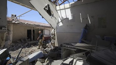 رجل يمشي وسط انقاض مستشفى مدمر في مدينة عفرين بسوريا (13 حزيران 2021، أ ب).