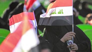 العلم العراقي مرفوعاً خلال تجمّع انتخابي في العاضمة بغداد (أ ف ب).