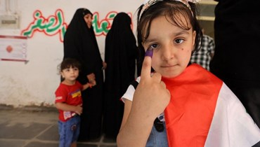 طفلة عراقية ترفع إصبعها بدلالة على مشاركتها رمزيّاً في الانتخابات العراقية (أ ف ب).