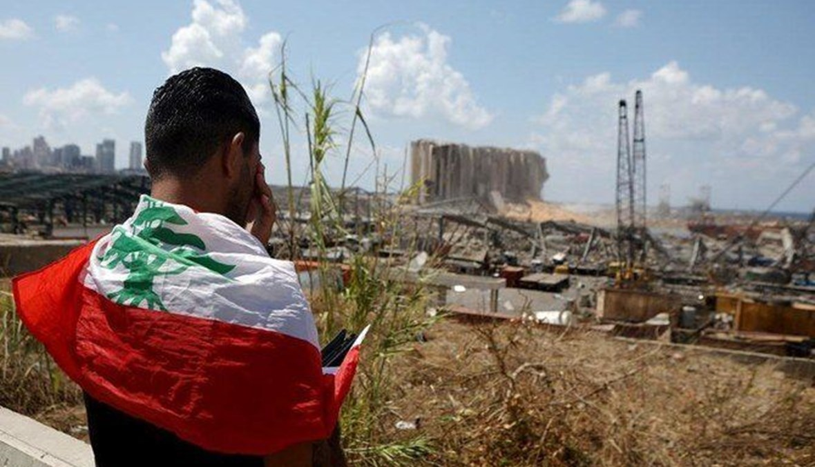 A man caped with the Lebanese flag looks at the damaged grain silos at the port of Beirut following the huge explosion that disfigured the Lebanese capital (AFP).