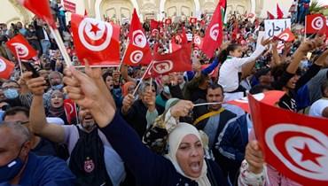 تونسيون يرفعون الأعلام الوطنية خلال مسيرة ضد سعيد في شارع الحبيب بورقيبة في العاصمة تونس (10 ت1 2021، أ ف ب).