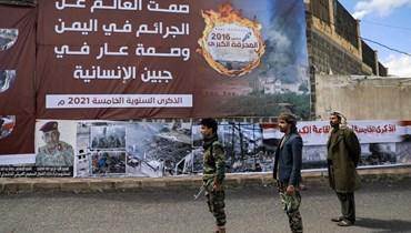 مقاتلون موالون للحوثيين يقفون بجانب لافتة خلال إحياء الذكرى الخامسة لغارة جوية شنتها قوات التحالف على مبنى قاعة عزاء في العاصمة صنعاء (9 ت1 2021، أ ف ب).