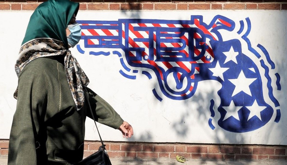 امرأة ترتدي قناعاً طبياً تمر أمام لوحة جدارية تصور مسدساً مرسوماً بألوان العلم الأميركي (أ ف ب).