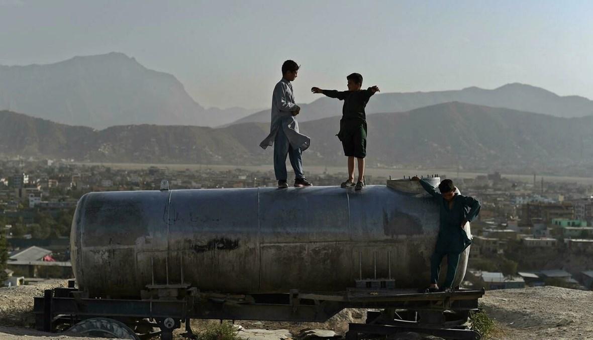 أولاد أفغان يلعبون فوق صهريج ماء على تلة تطل على كابول (أ ف ب).