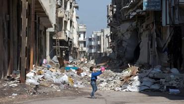 طفل يلعب بالكرة في أحد أحياء حمص المدمّرة (أ ف ب).