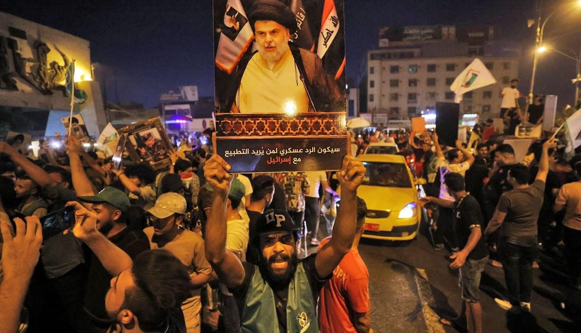 مناصر لزعيم التيار الصدري مقتدى الصدر يرفع صورته بعد صدور نتائج الانتخابات في بغداد (أ ف ب).