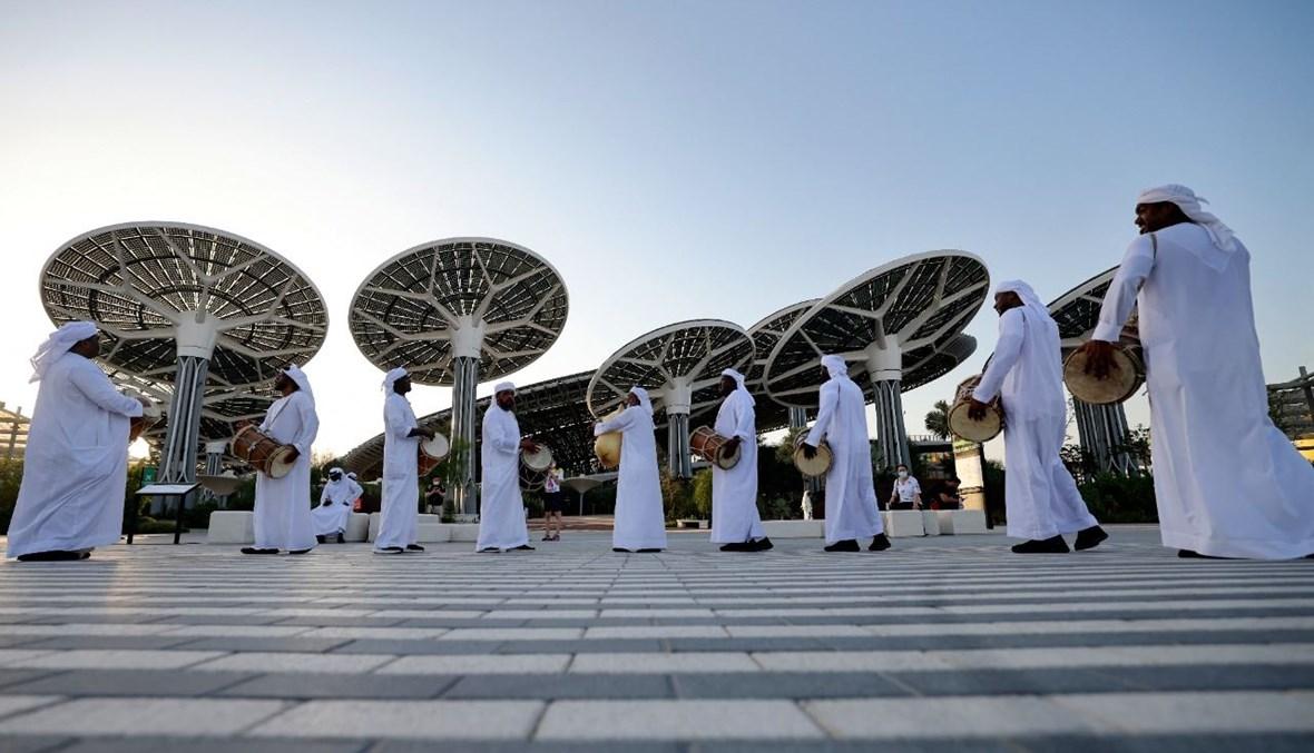 مجموعة من الموسيقيين الإماراتيين التقليديين يقدمون عرضًا عند مدخل معرض إكسبو 2020 بدبي  (6 ت1 2021، أ ف ب).