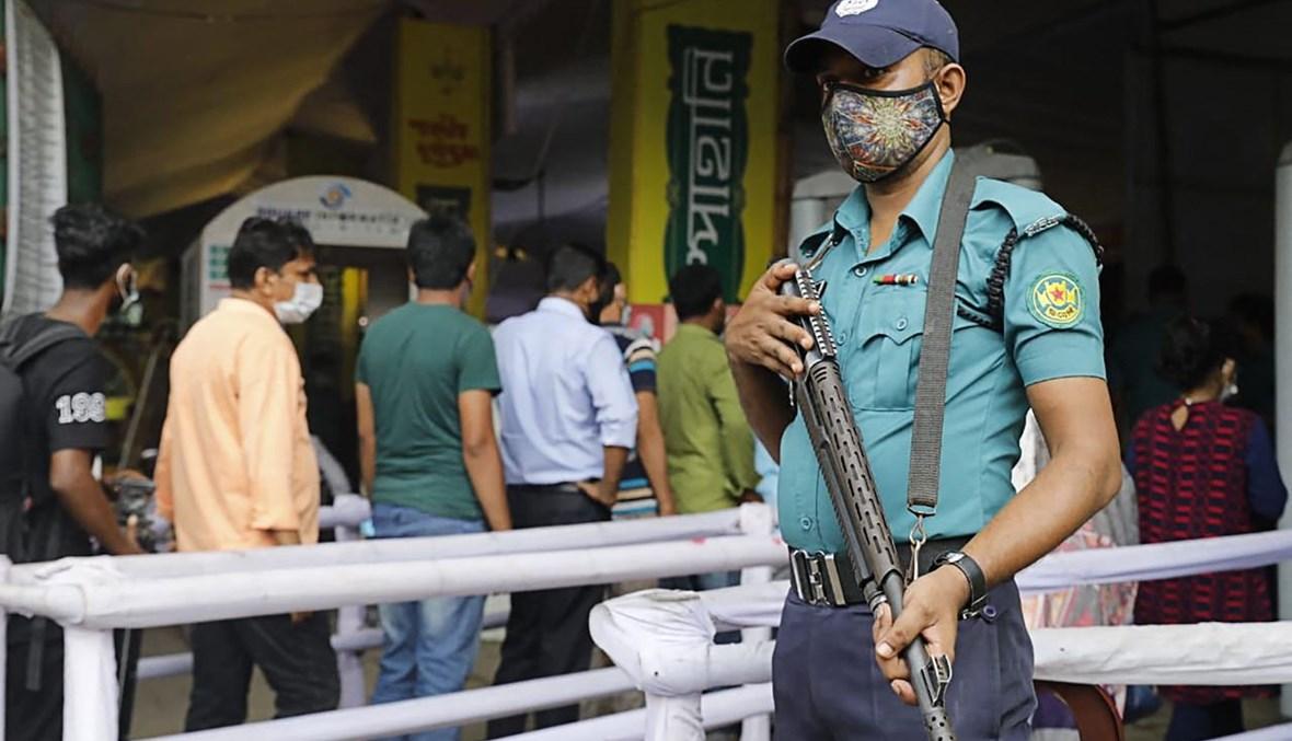 شرطي يحرس معبد دكيشواري خلال مهرجان دورغا بوجا في دكا (14 ت1 2021، أ ف ب).
