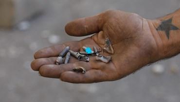 رجل يحمل فراغات الرصاص (تصوير مارك فياض وحسام شبارو)
