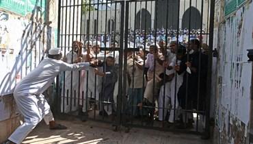 محتجون يحاولون كسر بوابة مغلقة للمسجد الوطني خلال تظاهرة بعد صلاة الجمعة في دكا (15 ت1 2021، أ ف ب).