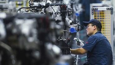 عامل ينتج محركات شاحنات في مصنع بمدينة هانغتشو في مقاطعة تشجيانغ شرقي الصين (أ ف ب).