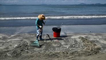 عامل ينظف زيت النخيل تسرب من باخرة على شاطئ في هونغ كونغ (الصورة نقلاً عن AFP)