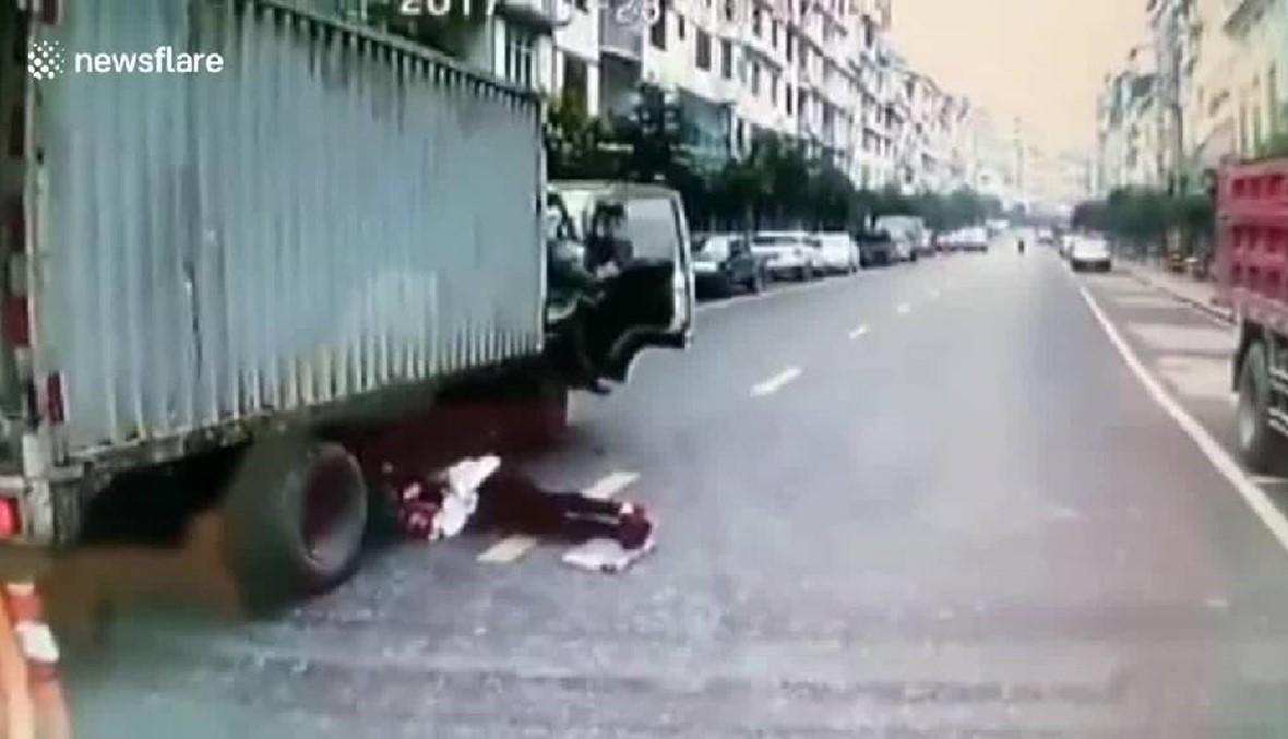 بالفيديو- انزلقت تحت الشاحنة لتتجنّب الدهس... استقرّ جسدها بين العجلتين ونجت بأعجوبة