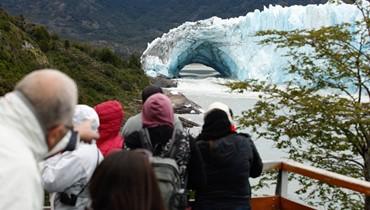 """سياح يلتقطون صورا لجبل """"بيريتو مورينو"""" الجليدي في حديقة """"لوس غلاسياريس"""" الوطنية في مقاطعة """"سانتا كروز"""" الأرجنتينية في 11 آذار 2018. قوس من الجليد تشكّل بين الجبل الجليدي وضفة بحيرة """"أرجنتينو""""، وبدأ ينهار في الماء السبت 10 آذار، في عرض طبيعي لا يحصل سوى مرة واحدة فقط كل سنوات عدة. مثل هذه الأقواس تتش"""