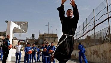"""راهب فرنسيسكاني يلعب كرة السلة مع أولاد فلسطينيين في مدرسة """"تيرا سانتا"""" خلال دورة رياضية في مدينة #القدس_القديمة. الرهبان الفرنسيسكان وصلوا الى #القدس قبل 800 عام، بتشجيع من مؤسس الرهبنة الفرنسيسكانية القديس فرنسيس الأسيزي. وقد حافظوا على الوجود المسيحي في الأراضي المقدسة طوال قرون (أ ف ب)."""