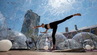 منعاً لانتشار فيروس كورونا... كنديّون يمارسون اليوغا داخل فقاعات بلاستيك (صور)