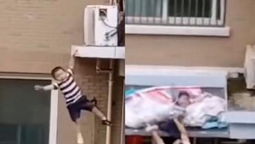 نجا من الموت... رجل يمسك بطفل سقط من الطبقة الخامسة في الصين (فيديو)
