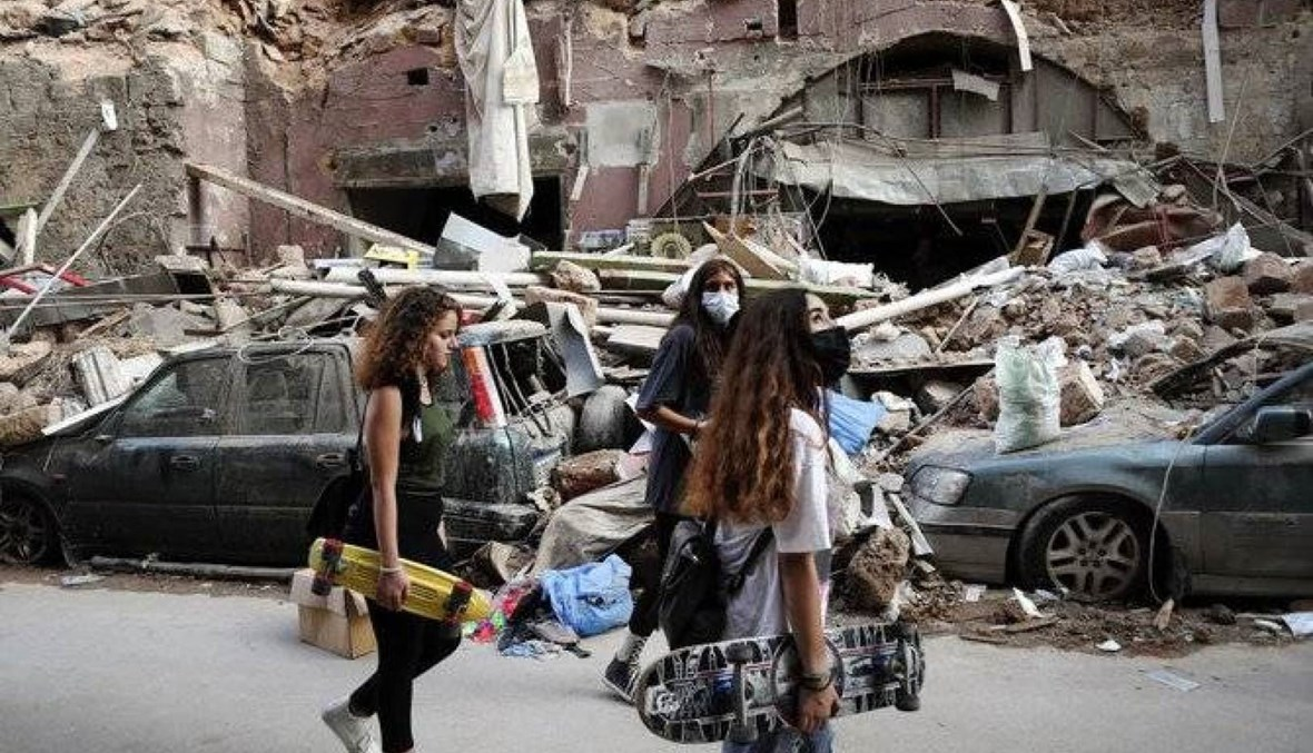Women walk past destroyed cars at a neighborhood near the scene of Tuesday's explosion that hit the seaport of Beirut, Lebanon, Friday, Aug. 7, 2020. (AP Photo)