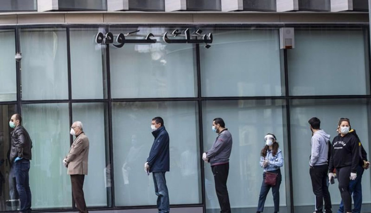 Clients wearing protective masks line up to use ATM machines outside a closed bank in Beirut, Lebanon. (AP Photo)