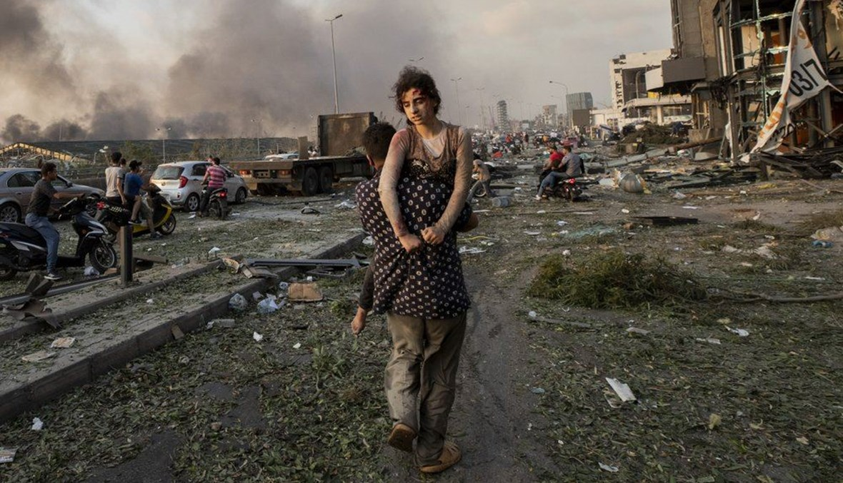In this Aug. 4, 2020 file photo, Hoda Kinno, 11, is evacuated by her uncle Mustafa, in the aftermath of a massive explosion at the port in Beirut, Lebanon. (AP Photo)