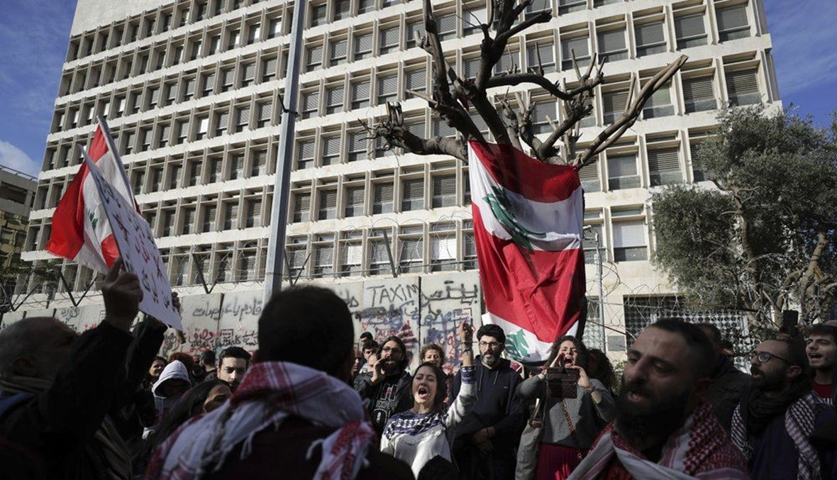 Anti-government protesters chant slogans, during ongoing protests against the Lebanese government in front of the Central Bank, in Beirut, Lebanon, Saturday, Feb. 1, 2020. (AP Photo)