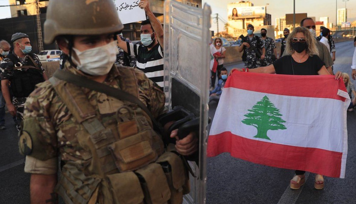 A Lebanese army soldier passes in front of an anti-government protester holding a national flag and blocking a main highway in Zalka on October 5,2020. (AP Photo)
