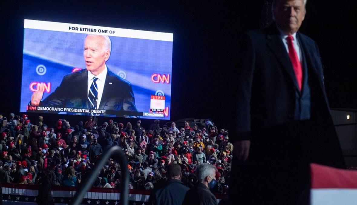 بايدن في خلفية الصورة خلال حفل انتخابي لترامب (أ ف ب).