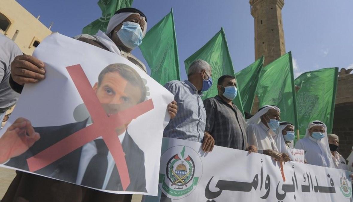 فلسطينيون يتظاهرون تنديداً بموقف الرئيس الفرنسي إيمانويل ماكرون في دير البلح بوسط قطاع غزة أمس.(أ ف ب)